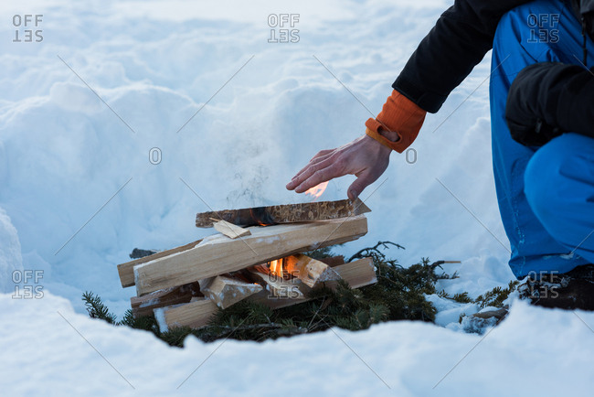 Man warming up by the bonfire during winter