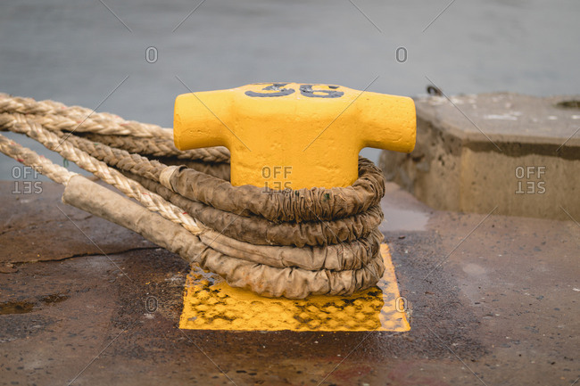Old mooring bollard with rope tied on pier