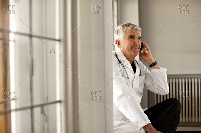 Senior male doctor sits in a corridor talking on his mobile phone