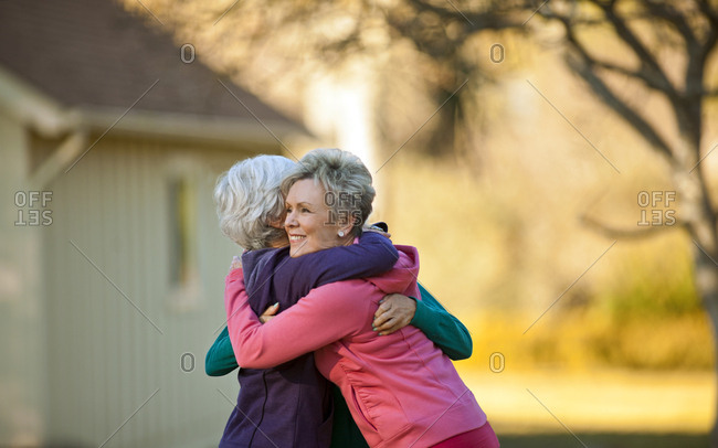 Three senior women hugging each other in a park