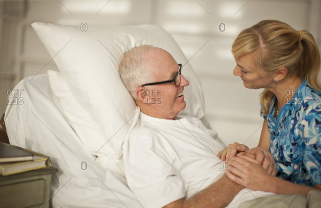 Young nurse holding the hands of an elderly patient