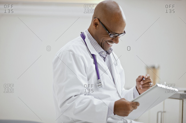 Smiling male doctor taking notes on a clipboard while sitting inside his office