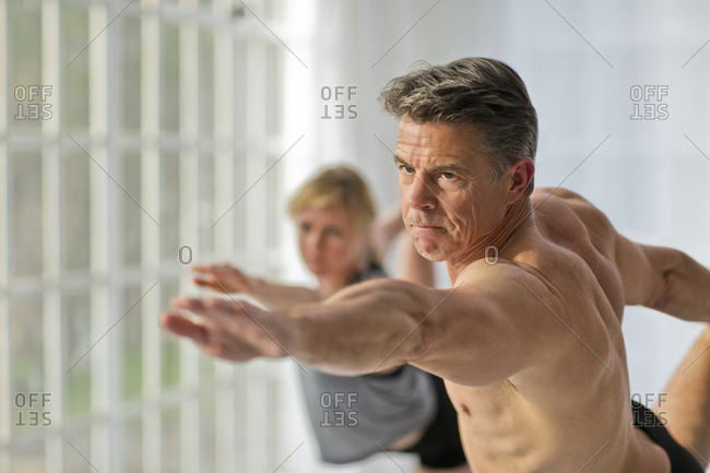 Mature man practicing the warrior pose during a yoga session