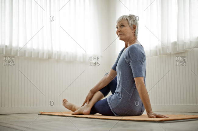 Mature woman practices peaceful yoga stretches in her home studio
