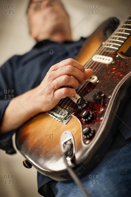 Mature adult man playing an electric guitar