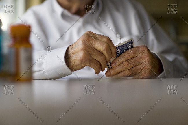 Elderly man plays cards by himself at the kitchen table
