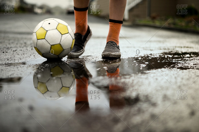 Boy playing with soccer ball in street