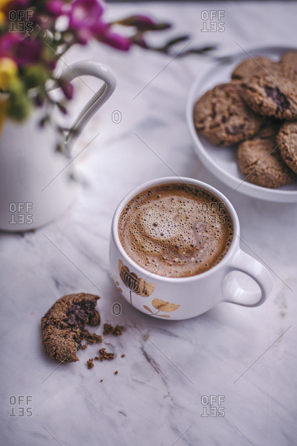 Chocolate chip cookies on a small white cake stand and a cup of coffee