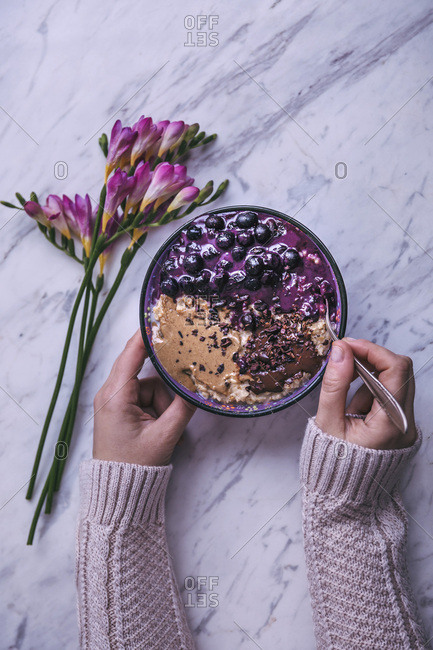 Woman eating bowl of oatmeal topped with blueberries, tahini and melted dark chocolate