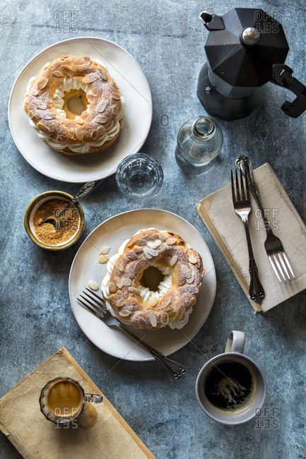 French pastries, coffee mugs and a glass with water on the table