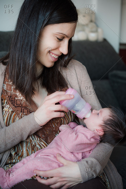 Smiling mother feeding her newborn baby daughter from bottle