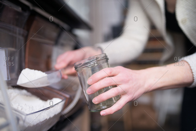 Person holding a glass jar and a scoop of flour