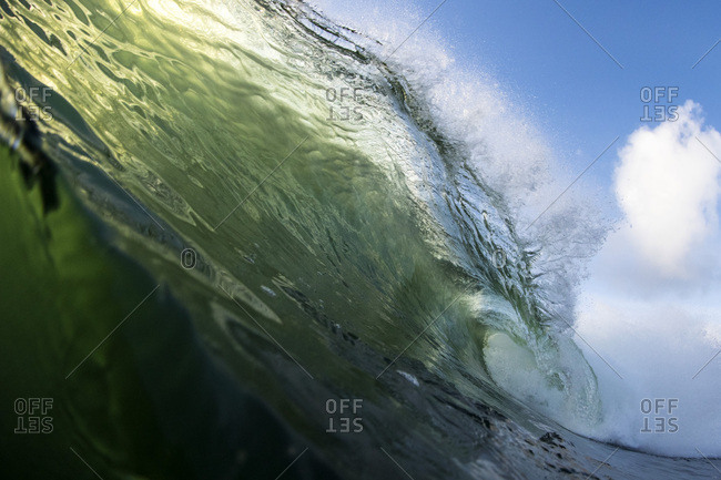 Watershot of backlit breaking wave
