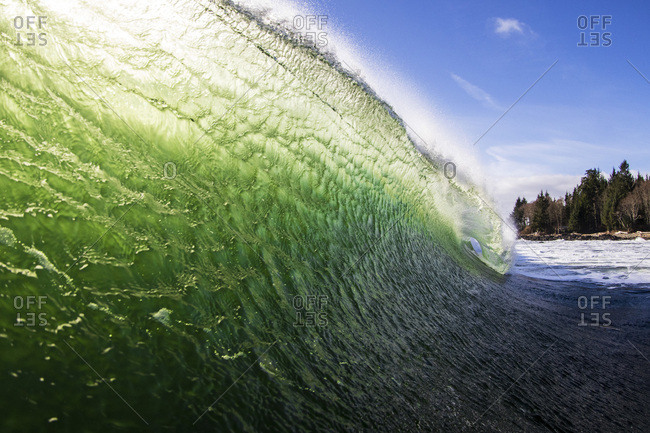 Watershot of face of breaking wave rippled by strong wind