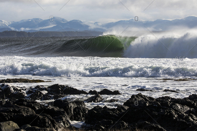 Wave breaking on rocky shoreline with forest and fog shrouded snowy mountains in distance
