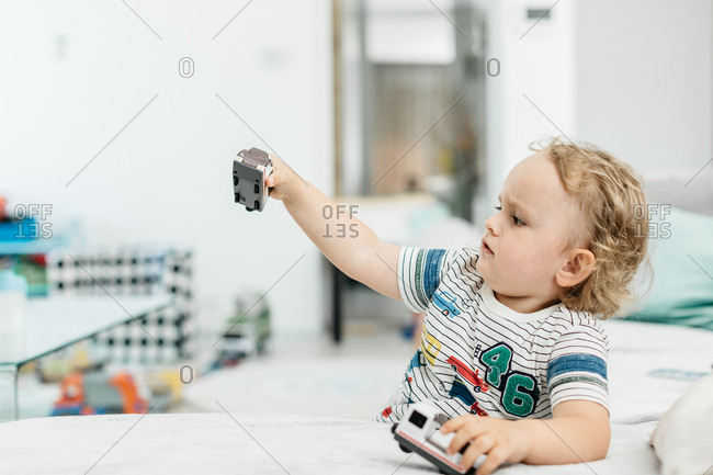 A young boy playing with toys on his own at home