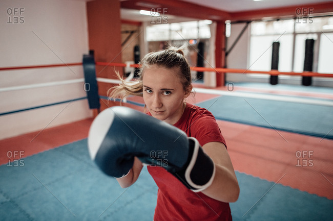 Close up of a young female kick boxer with boxing gloves punching towards camera