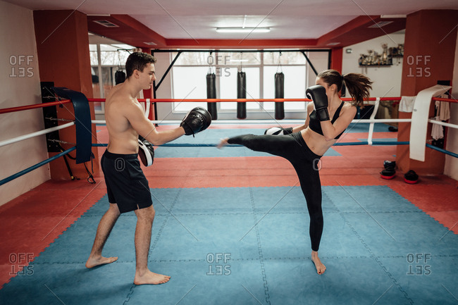 A male and a female boxer training kicks and punches in a boxing ring