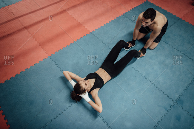 A man and a woman training together in a gym