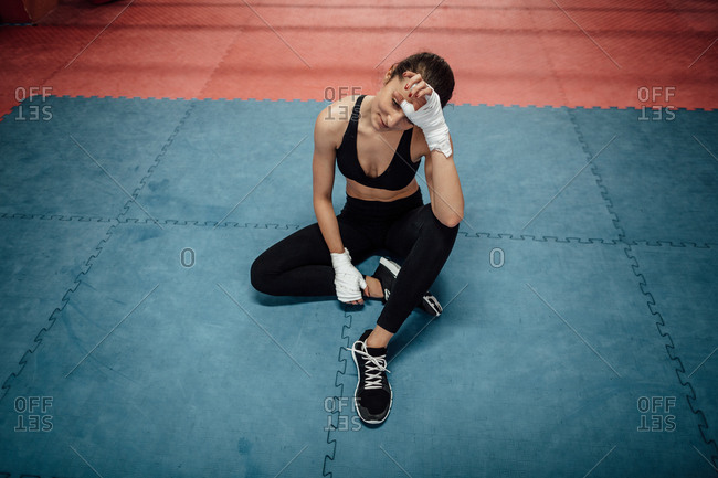 A portrait of a young female athlete relaxing after a workout in a gym