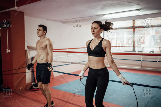 A man and a woman rope jumping together in a sports club