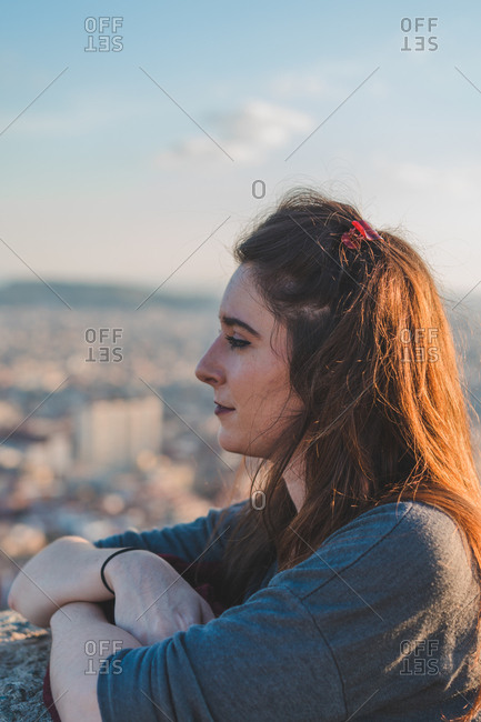 Side view of dreamy young woman leaning on fence and looking away on viewpoint.