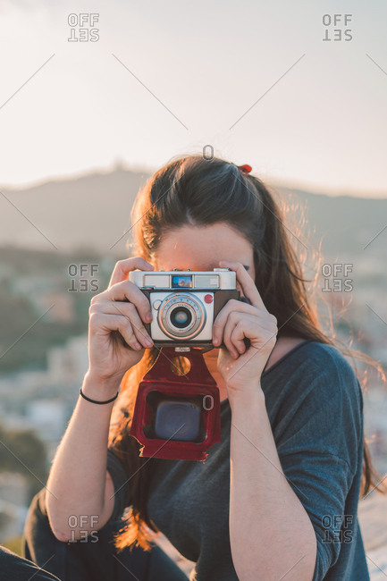 Cheerful woman focusing with camera