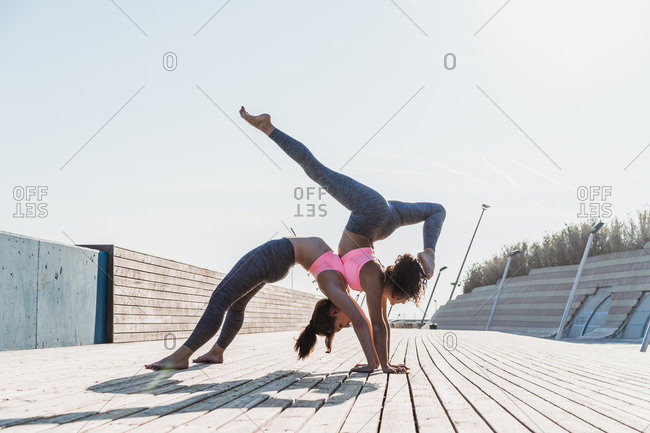 Side view of young women standing in asana and doing pair yoga together.