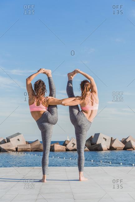 Women standing in asana on quay