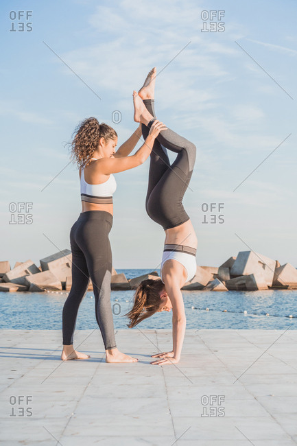 Side view of young fit women stretching and standing upside down on embankment.