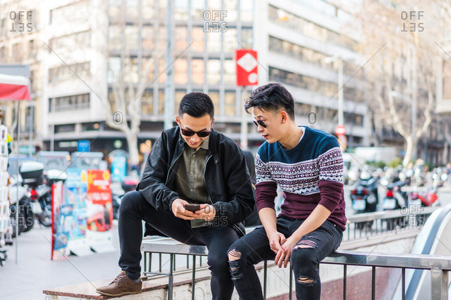 Young stylish men watching phone on street