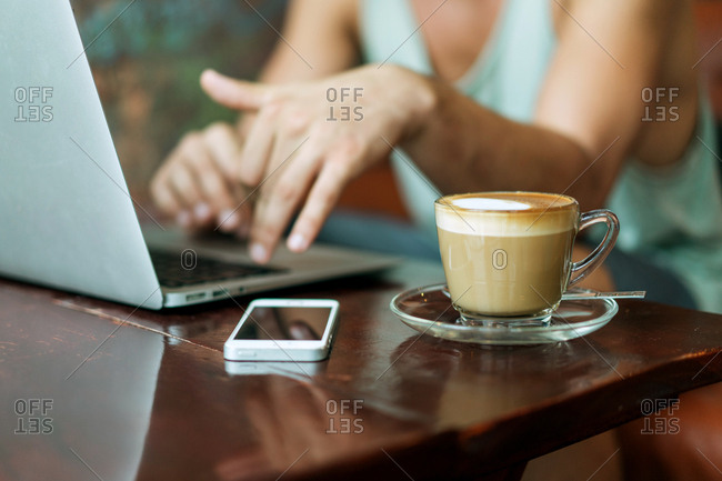 Table with coffee, smartphone and laptop used by unrecognizable person.