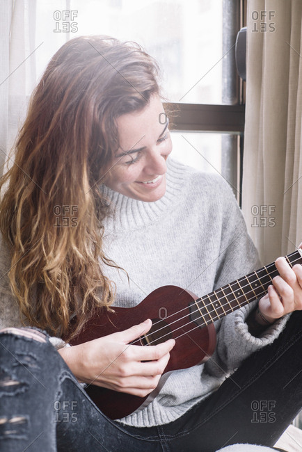 Cheerful adult woman sitting at home and playing ukulele at home.