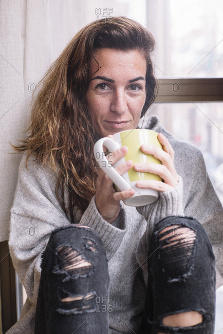 Cheerful woman relaxing with cup