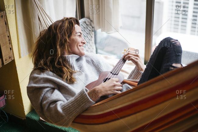 Cheerful woman playing ukulele