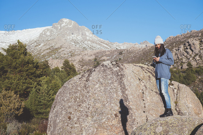 Woman with smartphone on rock