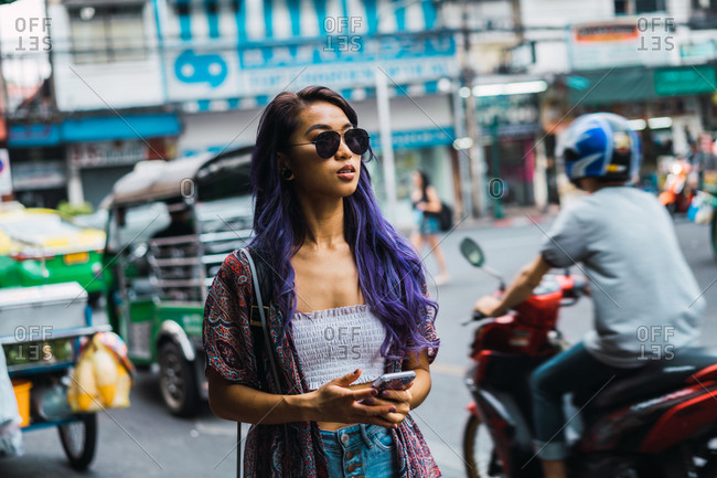 Pretty young Asian woman in sunglasses with smartphone on city street.