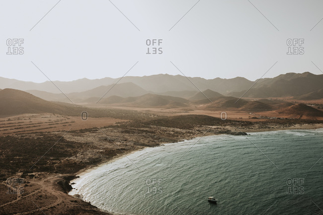 View to coastal hills and calm ocean in the bay with small boat sailing.