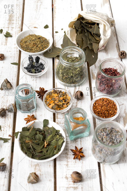 Composed glassware with various spices and herbs arranged on wooden table.