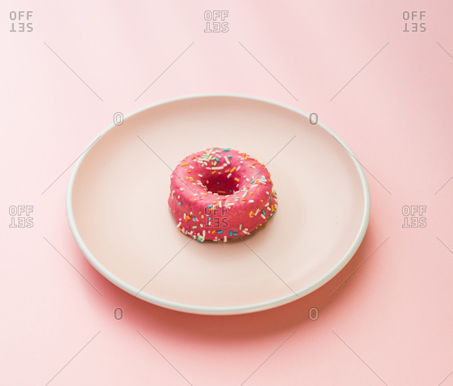 Minimalist arrangement of glazed dessert with sprinkles on white round plate.
