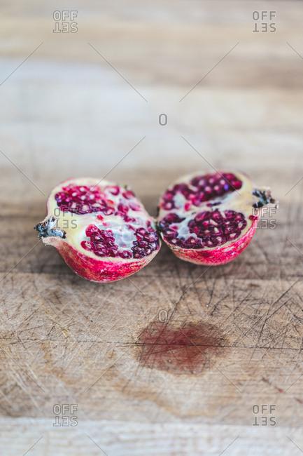 Fresh pomegranate halves on wood