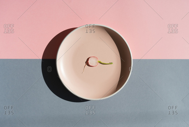 Flat lay of thin radish slice lying on clean round plate on two colored background in sunlight.