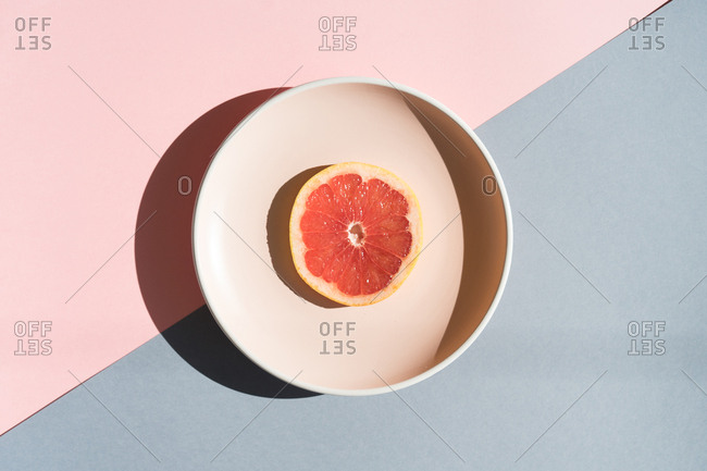 Flat lay of delicious grapefruit slice served on plate above colorful background.
