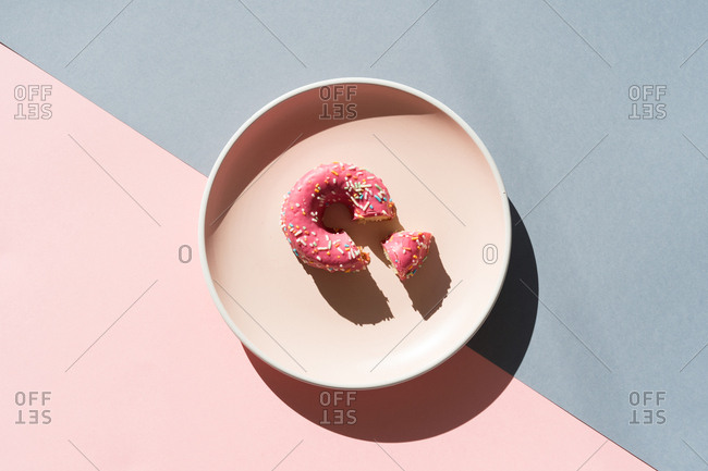 Top view of round plate on two colored backgrounds with glazed colorful doughnut.