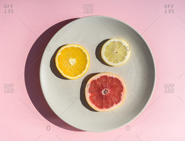 Flat lay of round plate with colorful slices of orange and lemon and grapefruit.