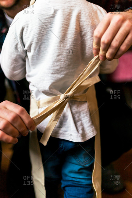 Unrecognizable man tying bow on apron of con playing chef.