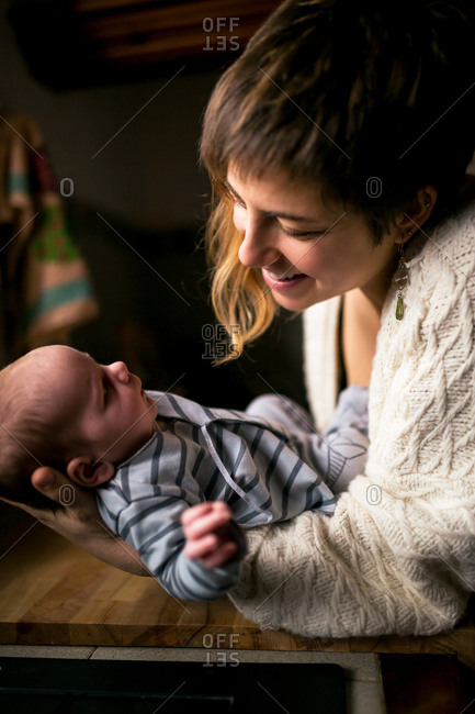 Smiling woman playing with infant child