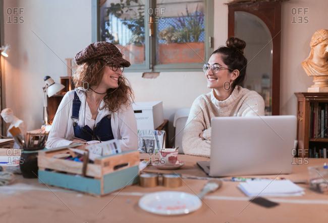 Cheerful women at laptop in workshop