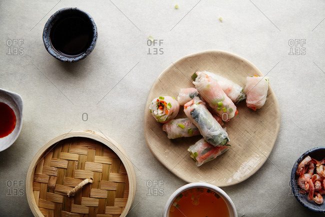 Spring rolls with marinated vegetables and shrimps on white textured background