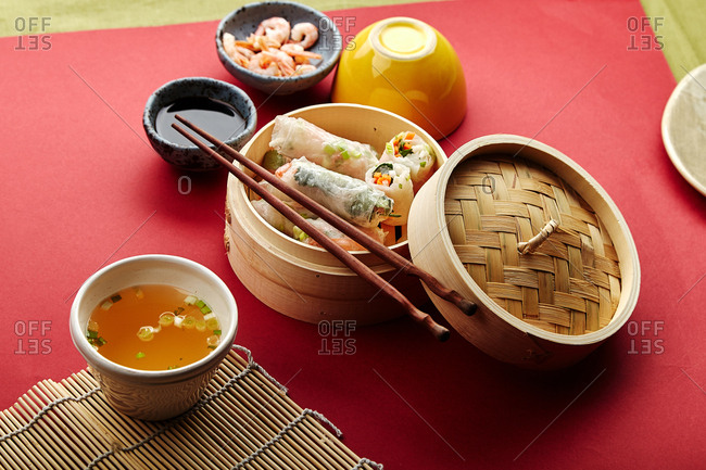Spring rolls with shrimps and marinated vegetables in bamboo steamer on red background